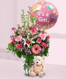 Pink flowers in a clear glass vase accompanied by a stuffed bear and mylar balloon that says