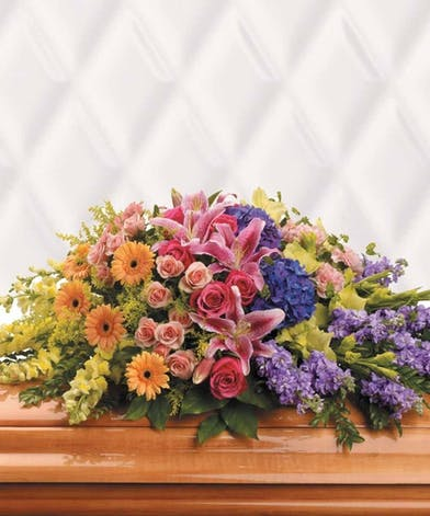 Bright casket spray in orange, pink, purple and green flowers.