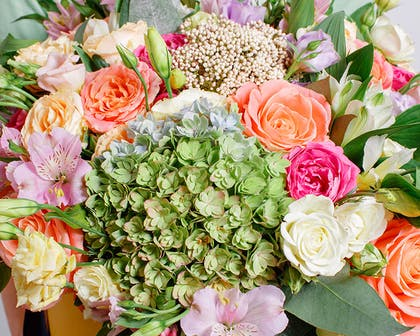 A colorful bouquet of orange and pink hydrangea in a large bouquet
